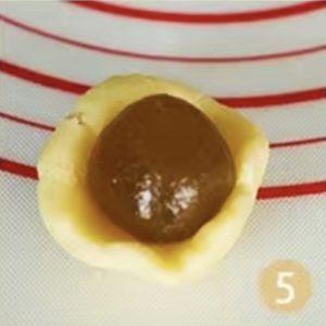 將餅皮滾成圓球,用手掌壓平,再將餡放在上面。